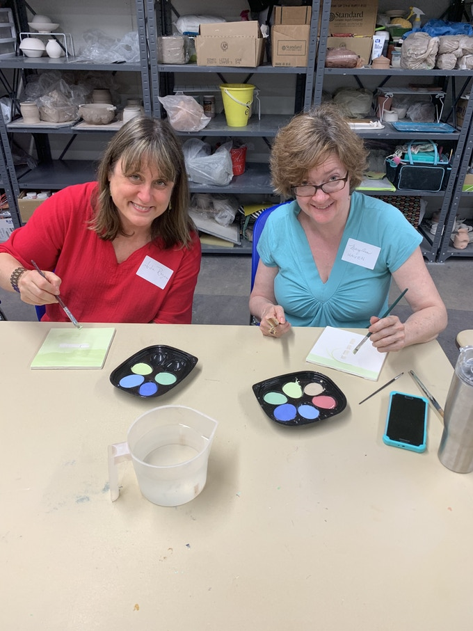 Local literary artist Aida Rogers and visual artist Mary Ann Haven paint tiles for An Array of Remarkable SC Women