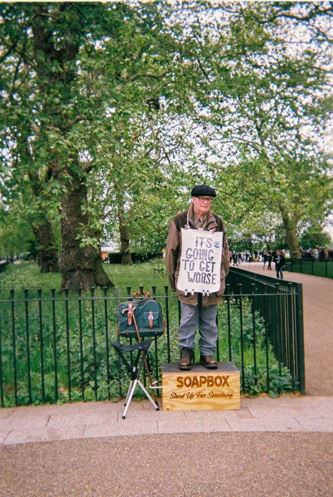 """Soapbox, Speakers' Corner, by Lui Saatchi. January 2020 in MyLondon calendar. """"This guy – his name is Bob – I know him from Speakers' Corner. I have known him for about 27 years now. He's always there on Sunday with a sign on his chest saying """"It is going to get worse"""" and I think he's right as compared to 27 years ago things have got worse economically, politically, socially, everything... That's Speakers Corner by Marble Arch. People come from all over London. Some people come from all over the world. It's on Sundays. For the chat. Politics, economics and everything. A very exciting place to be there."""" Lui goes to an art group run by 240 Project in west London."""