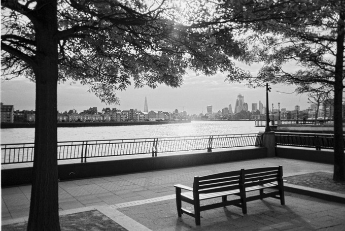"""Thames View, Canary Wharf, by Wes. August 2020 in MyLondon calendar. """"It's in Cabot Square, just off Canary Wharf. It's right at the river's edge where you've got the O2 Arena just behind you and the Canary Wharf banking section just behind you. I liked the sun shining through into this bench. It was sunset. It had rained that day and everything was nice and clear. When you look across London you get to see the Shard and you get to see all of Central London here as well. This was like the calm after the storm."""" Wes is connected to several homelessness-sector organisations."""
