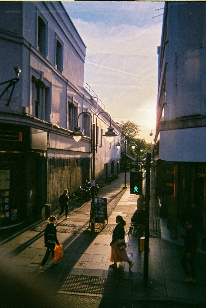 """Perfect light, Brixton, by Peter Nathan. September 2020 in MyLondon calendar. """"It's a photo of a street corner during the day. Because of the way that the sunlight was reflecting off the buildings, creating the shadows and the contrast it just literally reminded me of a street in the Victorian era with 21 Century buildings surrounding it and the whole essence of it just was perfect as a picture to take. It was difficult working on a 35mm [film] camera because I had no idea other than what I was looking at to judge the light perspective but I just went for it."""" Peter attends the Crisis photography group."""