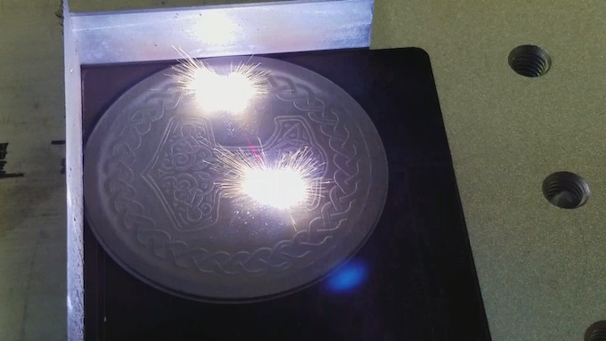 Engraving the graphic on a titanium medallion with our fiber laser