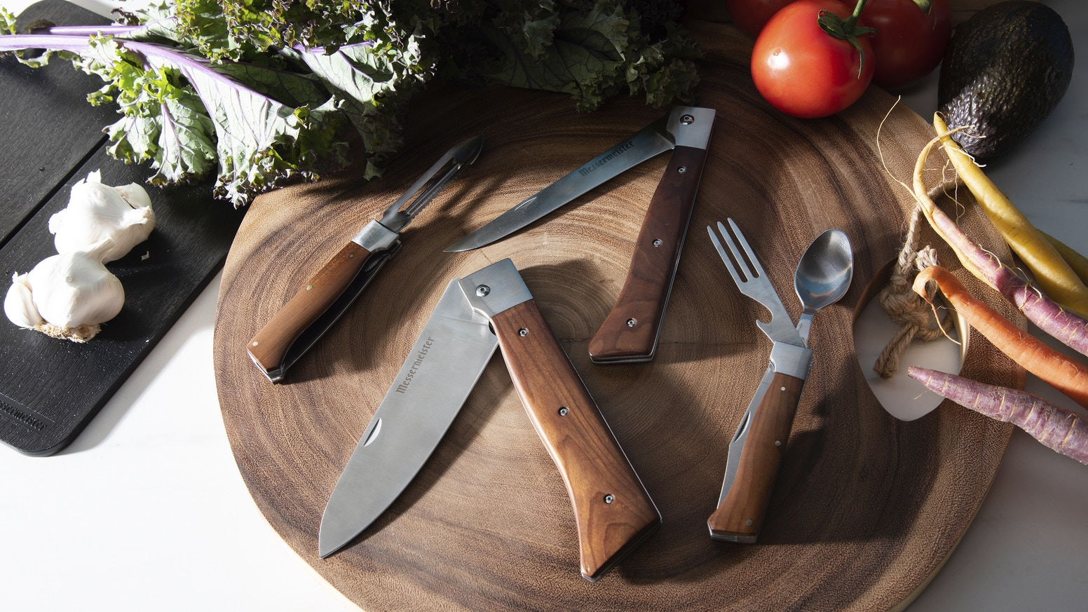 Outdoor cooking gear featuring full-sized, professional grade folding cooking knives. Chef's knife, fillet knife, peeler & camp utensil.