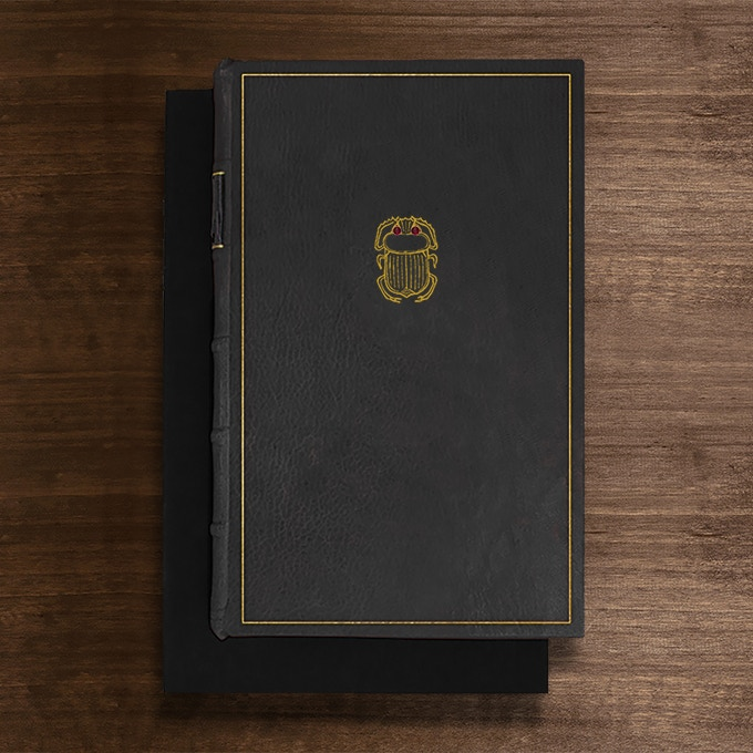 The Scarab Edition: Bound in Black Full-Leather with hand-marbled end papers. Hand tooled in genuine gold. Set with two cabochon carnelians. Presented in a suede lined clamshell box. Only 3 available.  The 3 reserved copies of the Scarab edition are currently being held for archival collections.