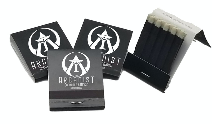"The Arcanist Bar Matchbooks. Final design may vary. ""Wild Bill"" likes to doodle in these when he's not playing in the house band, so some matchbooks may feature a surprise!"