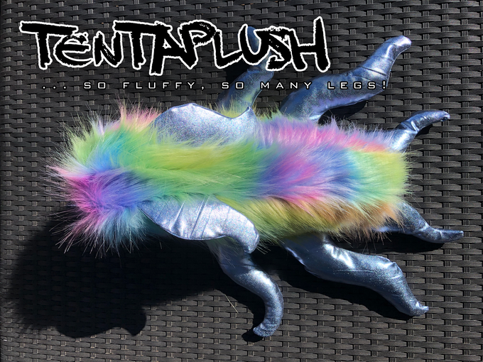 A prototype tentaplushie. [Image description: A plushie monster with a pastel rainbow (fake) fur body and silver lamé tentacles and horns.]