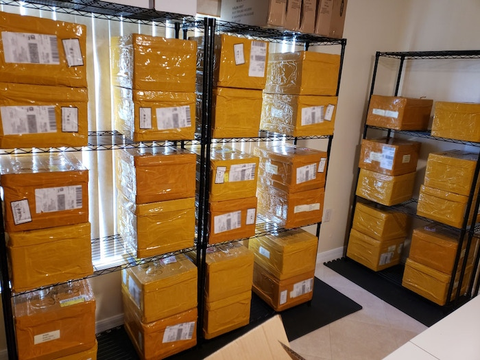 Some of the shelves in the intake room of the warehouse filled with White Widow #2 Kickstarter boxes!