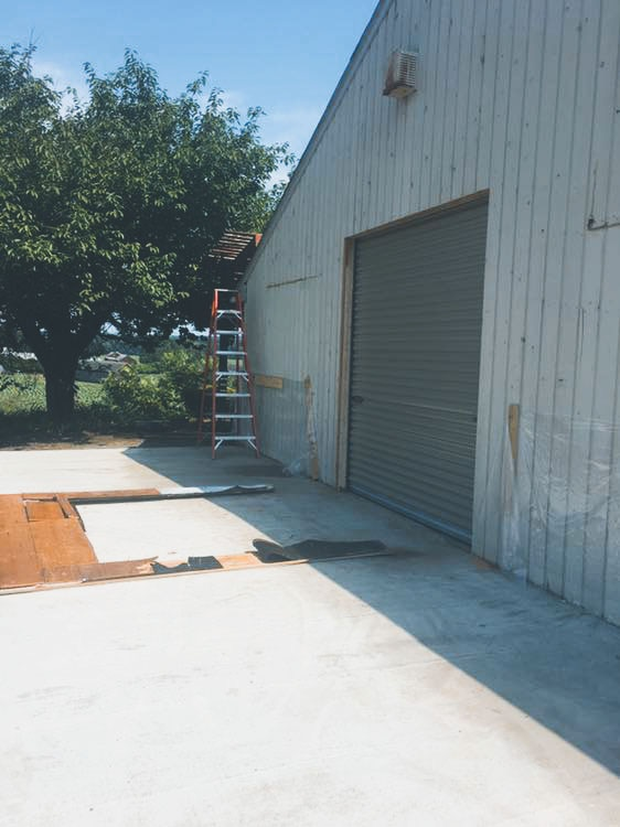 Concrete pad and garage door installed in July, leading in to the brewery.