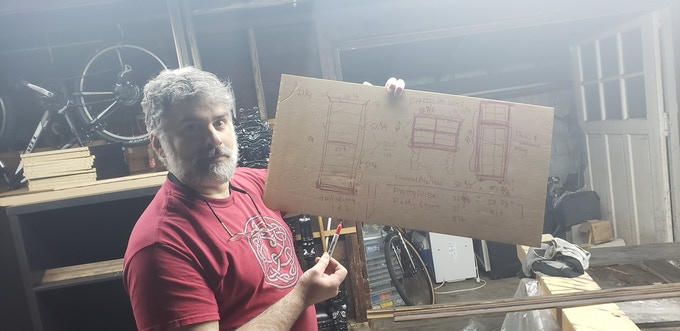 Andrew in the garage with the highly detailed and well-crafted plan to build the stage set pieces.