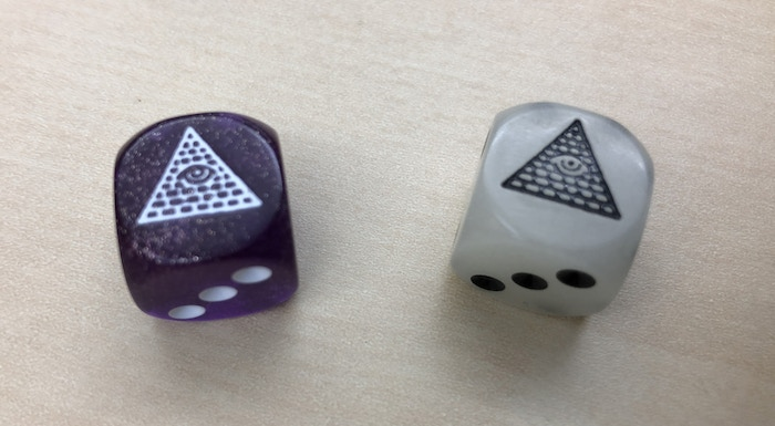 The two dice that are packed inside each Pocket Box game.