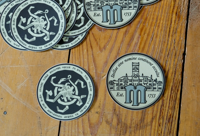 Ward off evil with two 3-inch vinyl stickers. One features the artifact and one of Miskatonic University's logo.