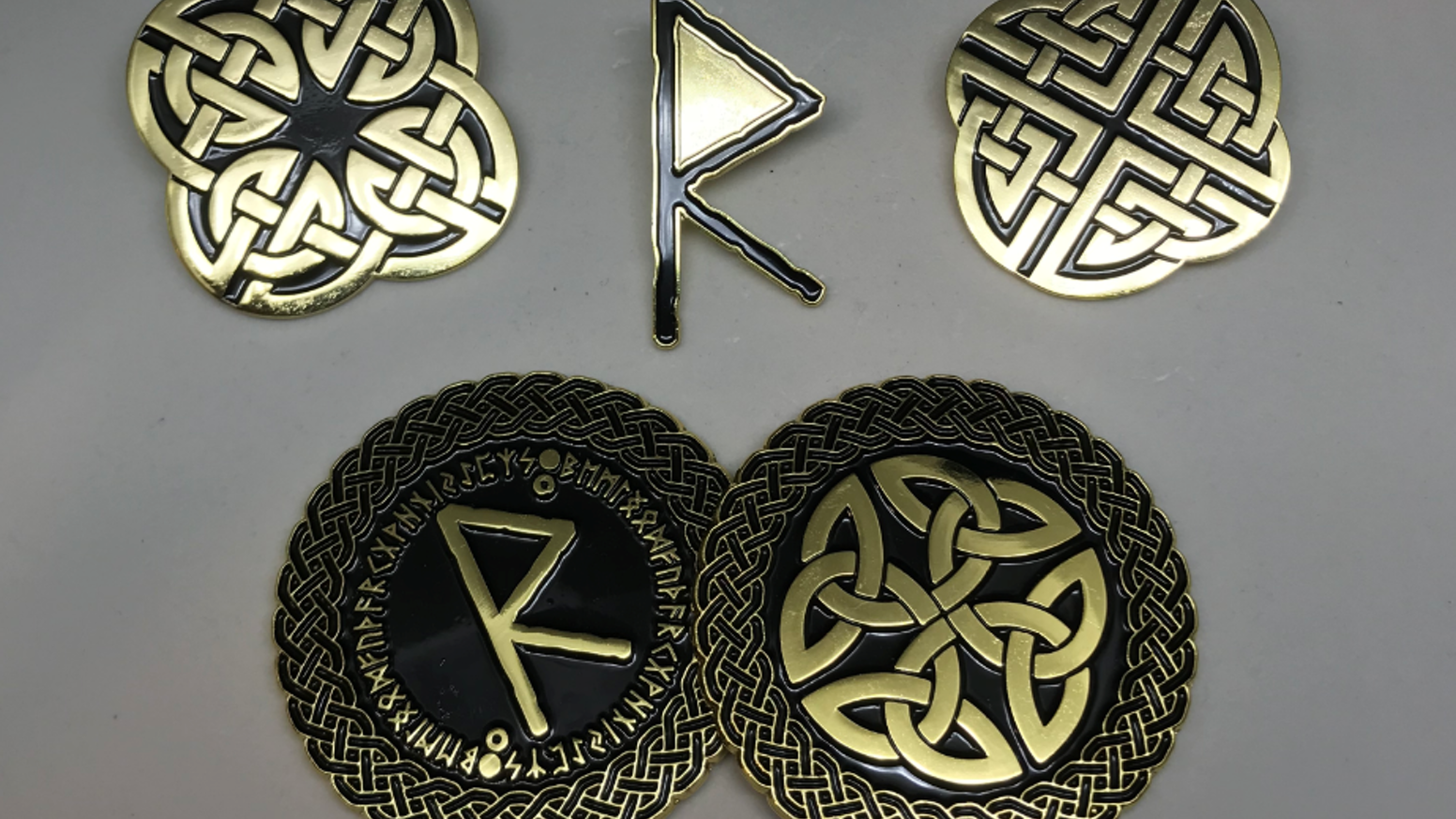 Enamel Pins and Coins with Celtic Knot and Norse Rune designs.
