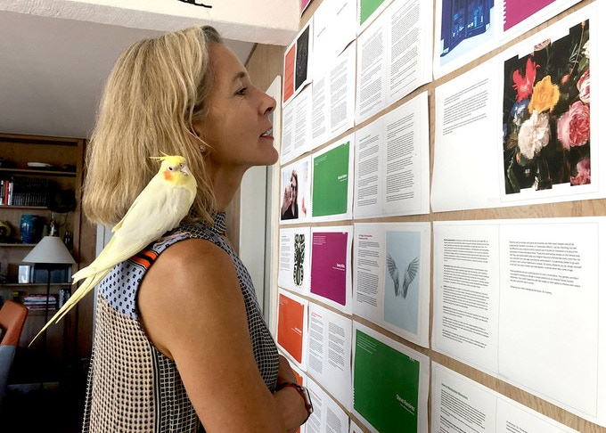 NEO.LIFE founder Jane Metcalfe and her cockatiel, Lemon, look over book pages