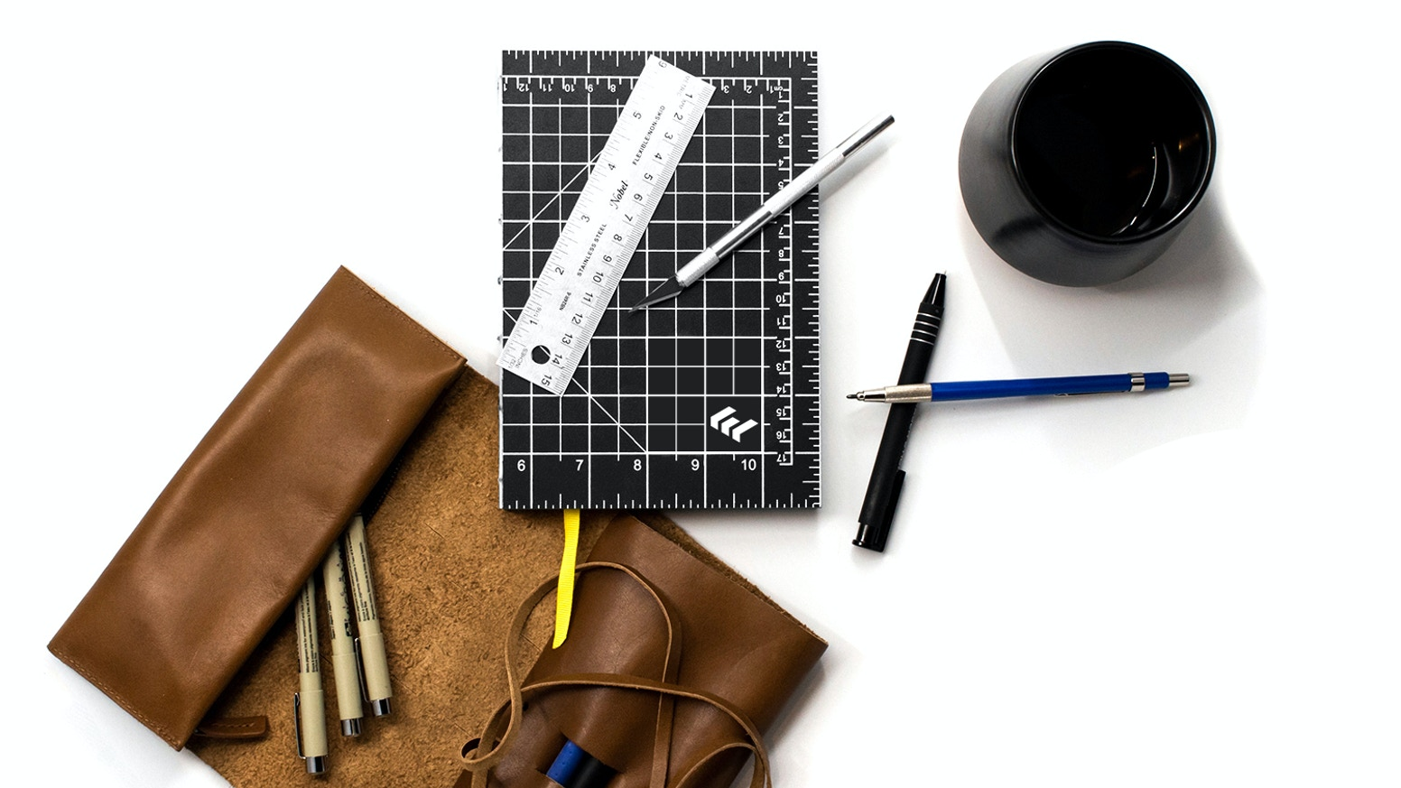 Hand-bound, eco-friendly bullet journals or notebooks with cutting mat covers and open-flat binding.