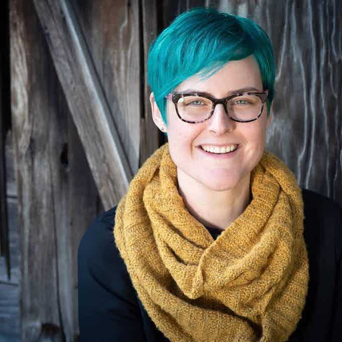 Kate Ristau, a white female with blue hair and a yellow scarf, smiling with a wooden background