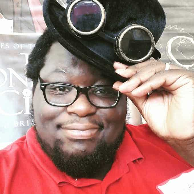 Brian W. Parker, illustrator of Wylde Wings, an african-american man with a red shirt, top hat, and steampunk goggles